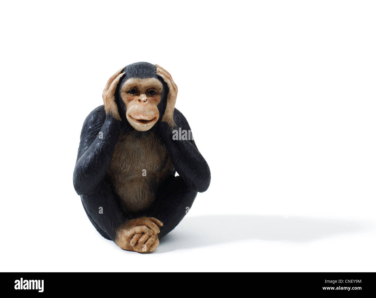 Studio shot of a toy monkey holding hands over ears. hear no evil - Stock Image