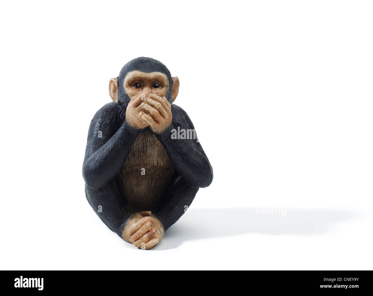 Studio shot of a toy monkey holding hands over mouth. speak no evil - Stock Image