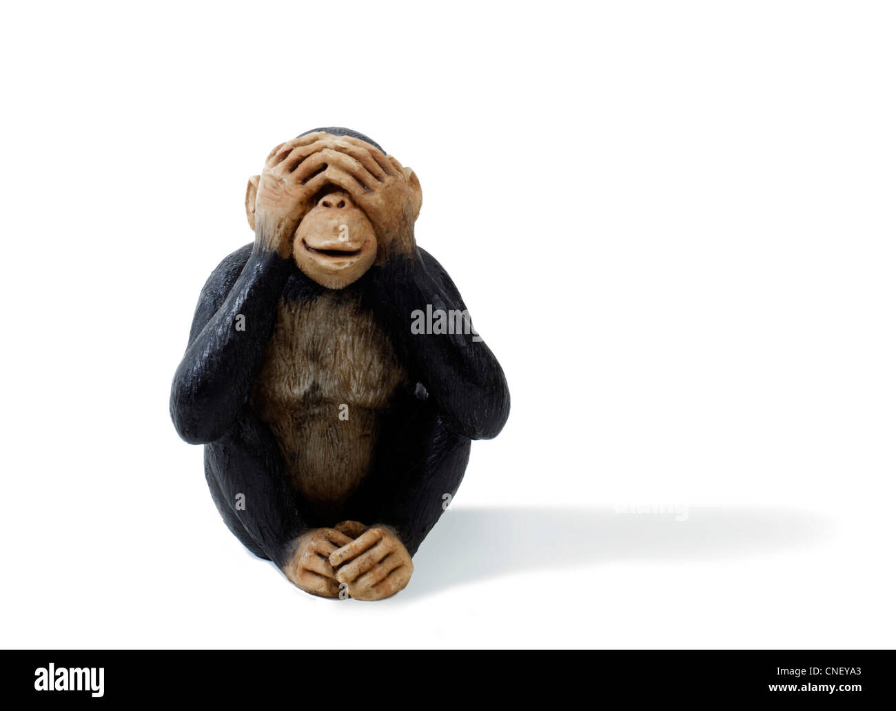 Studio shot of a toy monkey holding hands over eyes. see no evil - Stock Image