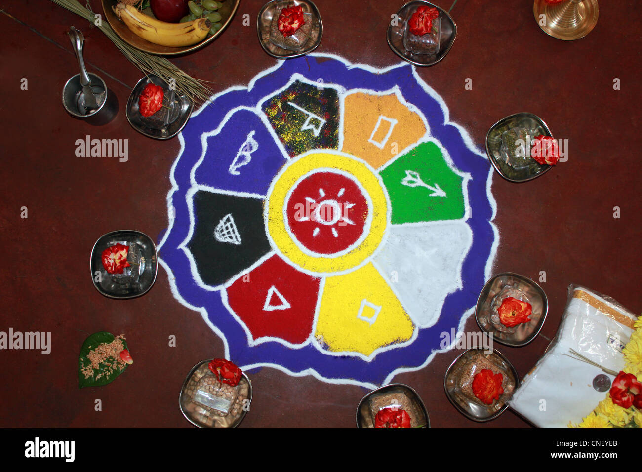 Colorful rangoli art with hindu puja items, flowers, dhoti and money Stock Photo