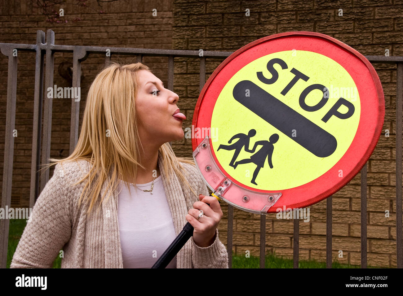 Beautiful woman holding a school traffic lollipop sign and her tongue sticking out during a photoshoot in Dundee Stock Photo