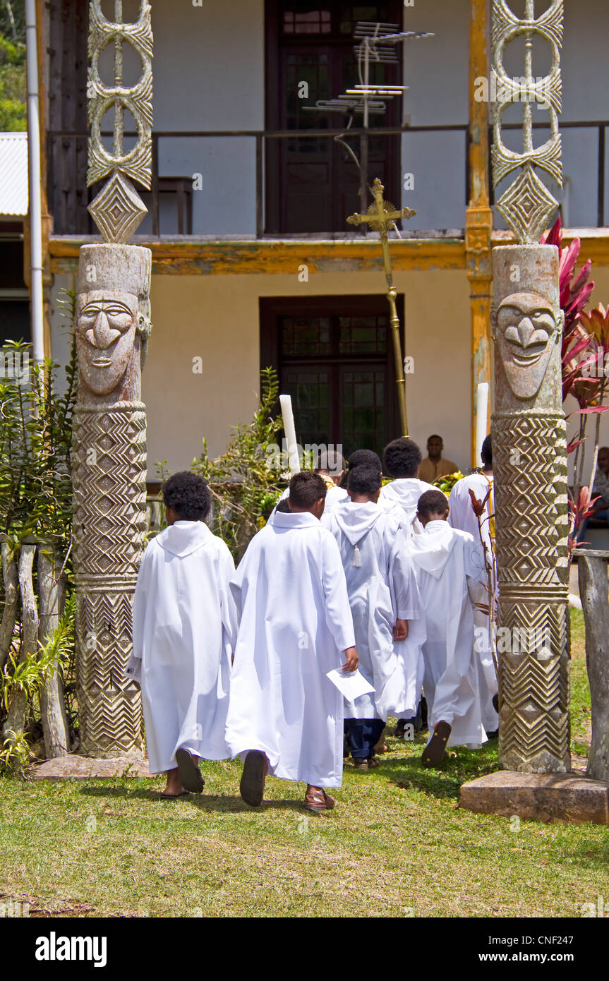 Altar boys after the mass carrying a cross and entering a