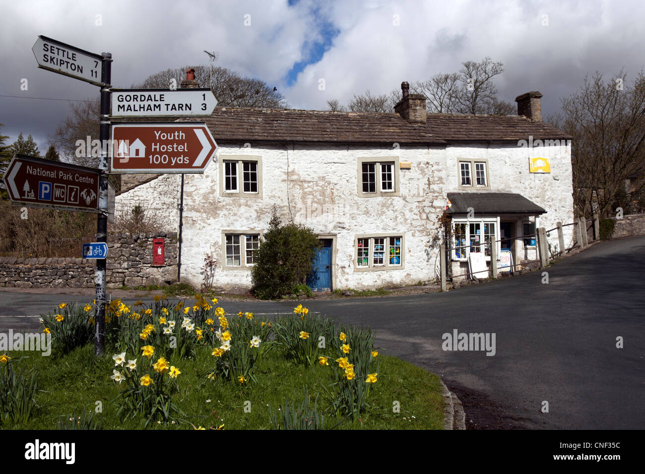 Subsided Property & Road Sign for Mallam Tarn, Gordale, Youth Hostel, Settle & Skipton in the Village of - Stock Image