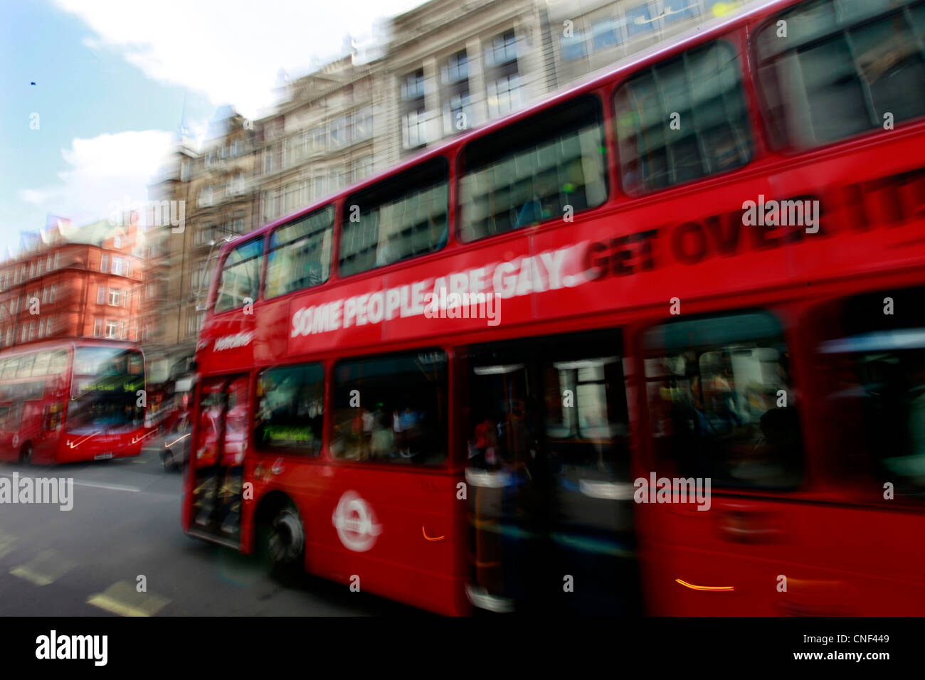 A London bus carries adverts from Stonewall promoting equal marriage with the slogan 'Some people are gay. Get - Stock Image