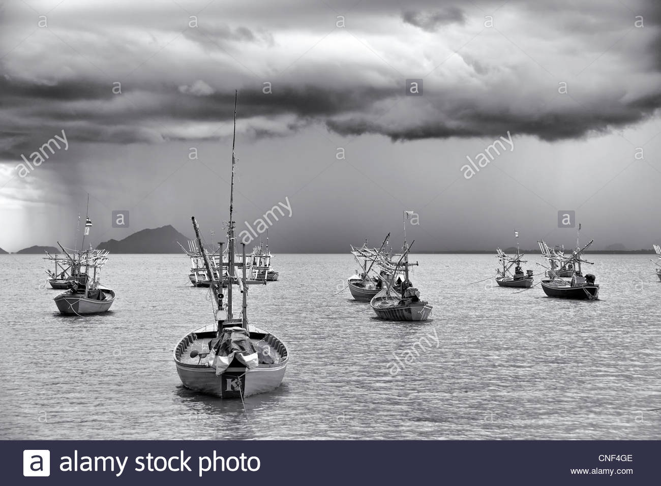 Stormy skies with visible descending rain moving into a fishing harbor Black and white photography - Stock Image