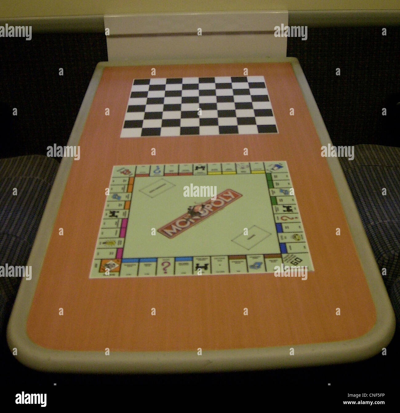 The unique combined Chess and Monopoly game boards on the table top surface - Stock Image