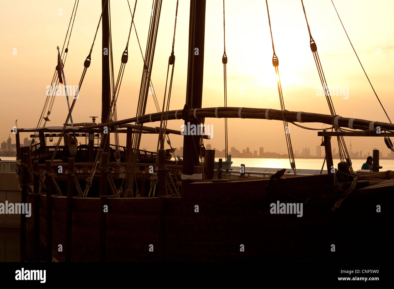 Silhouette of a Dhow at sunset in Kuwait with the city in the background. - Stock Image