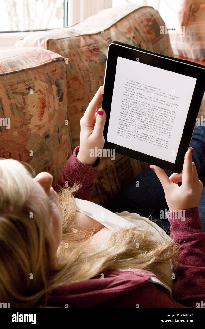 Teen girl reading an e-book on an iPad,  UK - Stock Image