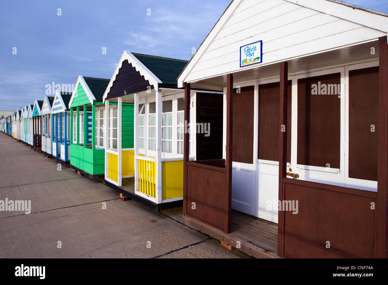 A row of different colored/coloured beach huts receding into the distance from the right to the left of the photo. - Stock Image
