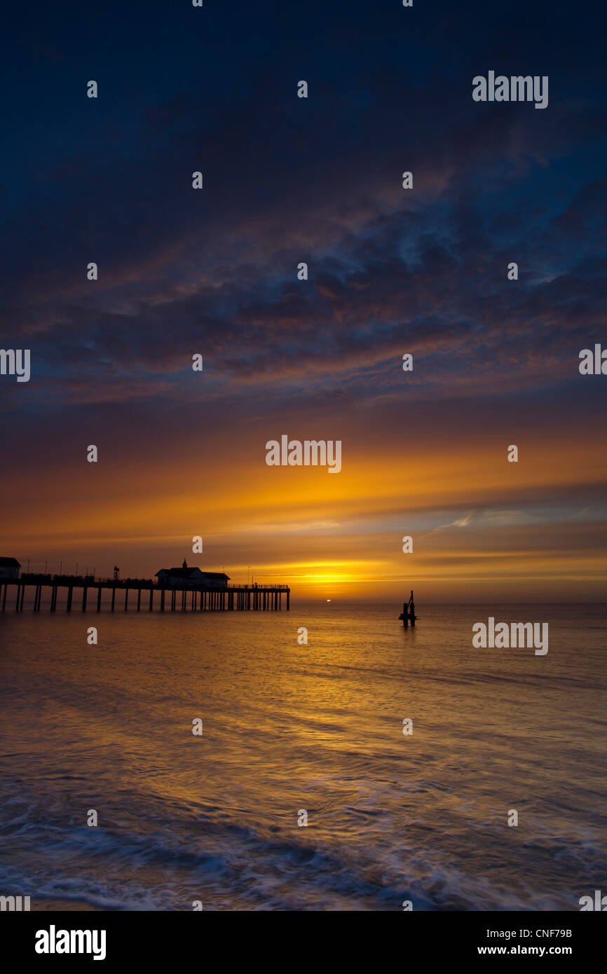 Southwold Pier Silhouetted against a beautiful sunrise, with the sun just above the water and dark clouds in the - Stock Image