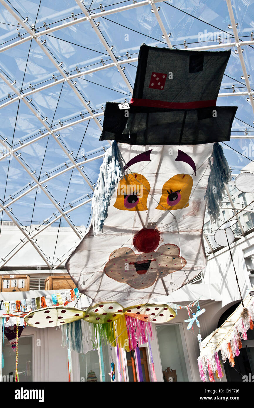 colorful humorous clown fantasy kite kites displayed under glass roof in courtyard of Museo de Arte Popular Mexico City Mexico Stock Photo