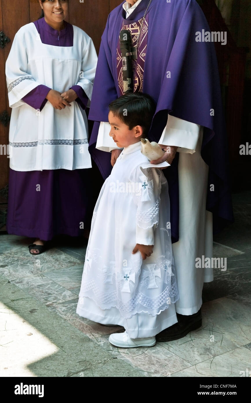 sweet faced young Mexican boy in embroidered white baptism robe stands with priest at Our Lady of Guadalupe church - Stock Image