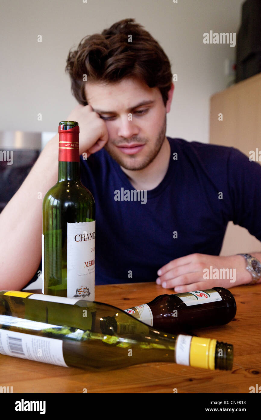 Drunk young man with hangover and empty bottles of wine and beer,  UK - Posed by a Model Stock Photo