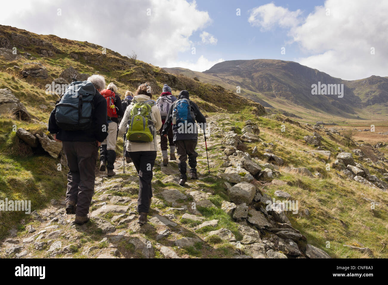 Ramblers group walking along the valley in mountains of Snowdonia National Park. Cwm Eigiau Conwy North Wales UK - Stock Image