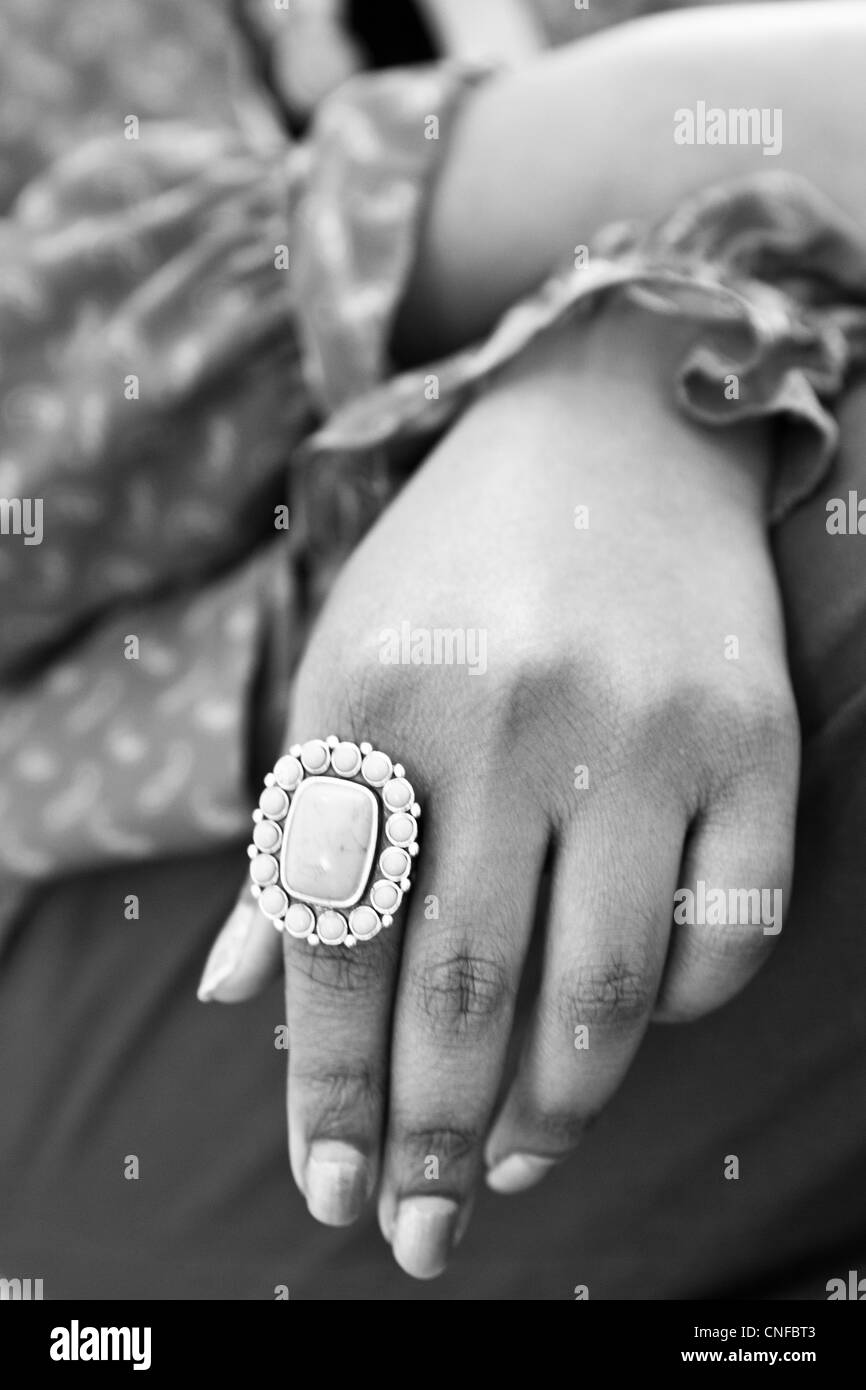 Artist's hand with large gem stone ring in close-up - Stock Image