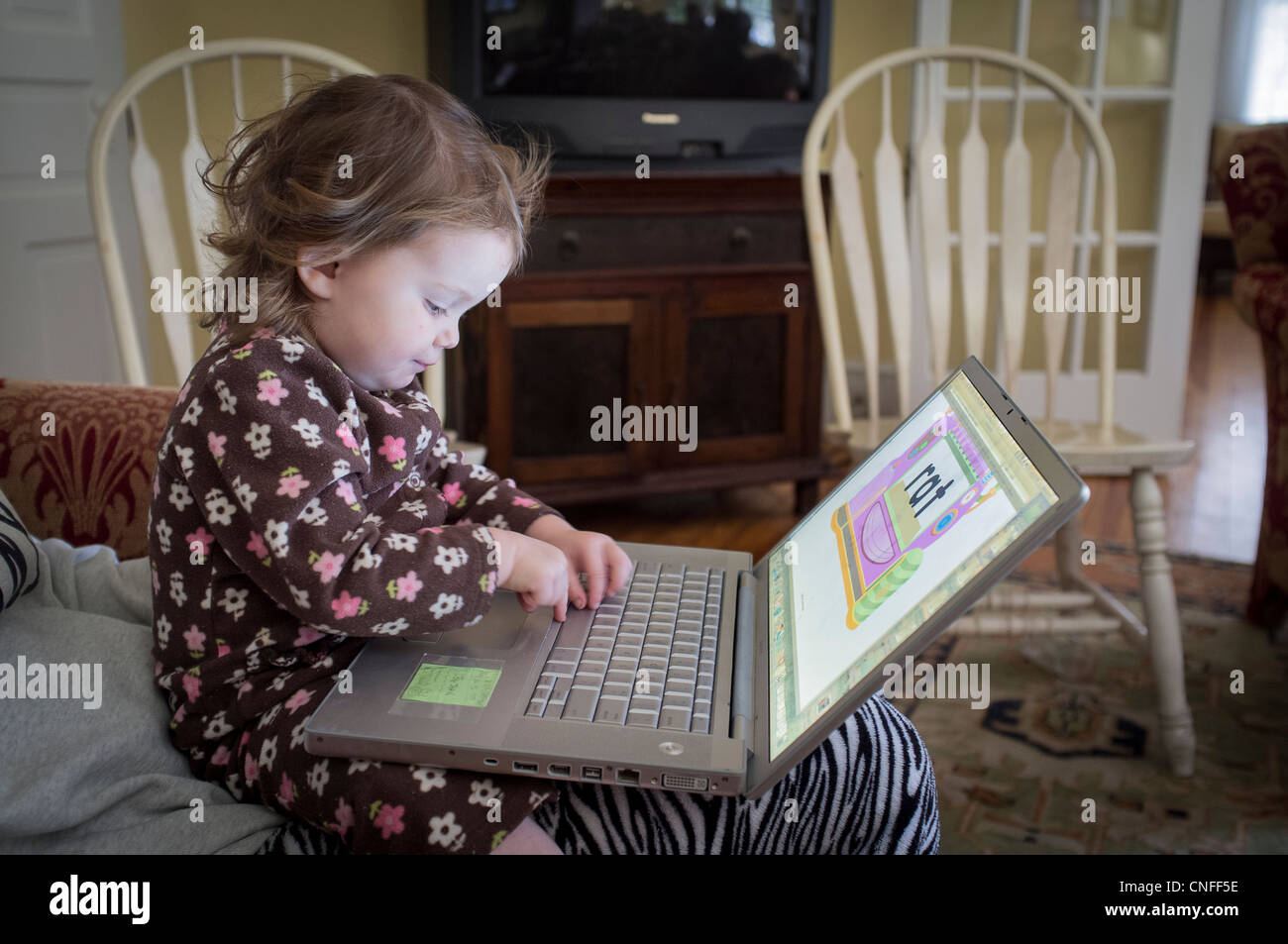 Baby learning on a computer - Stock Image