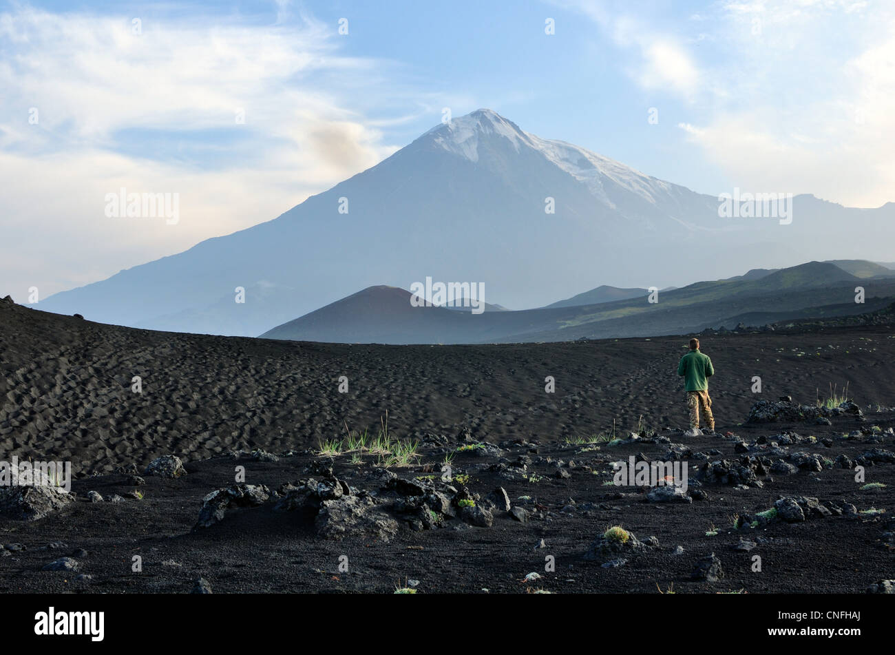 Man standing in lava field with Tolbachik Volcano in background, Kamchatka Peninsula, Russia - Stock Image