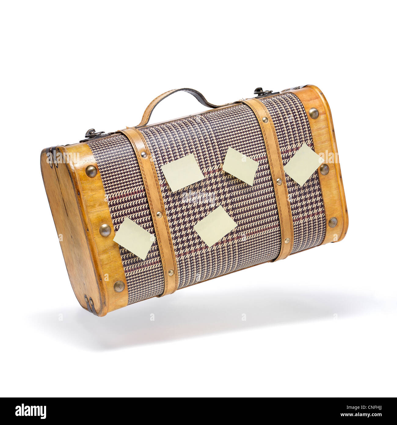 Classic suitcase in flying motion with blank post-it for messages. - Stock Image