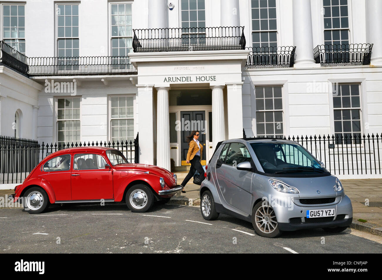 VW Beetle and Smart Car juxtaposition, Arundel House, Brighton, East Sussex, UK - Stock Image