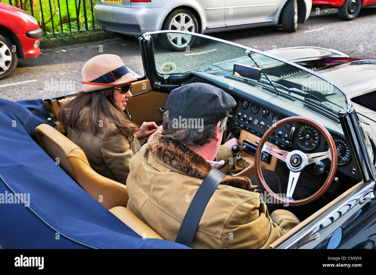 Lady and gent sitting in a E-type Jaguar classic car, London, England, UK - Stock Image
