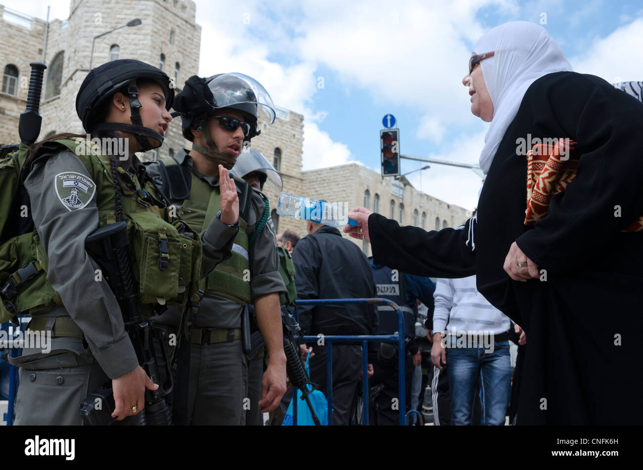 Male and female border patrol facing a Plestinian woman on Land Day. Damascus gate. Israel. - Stock Image