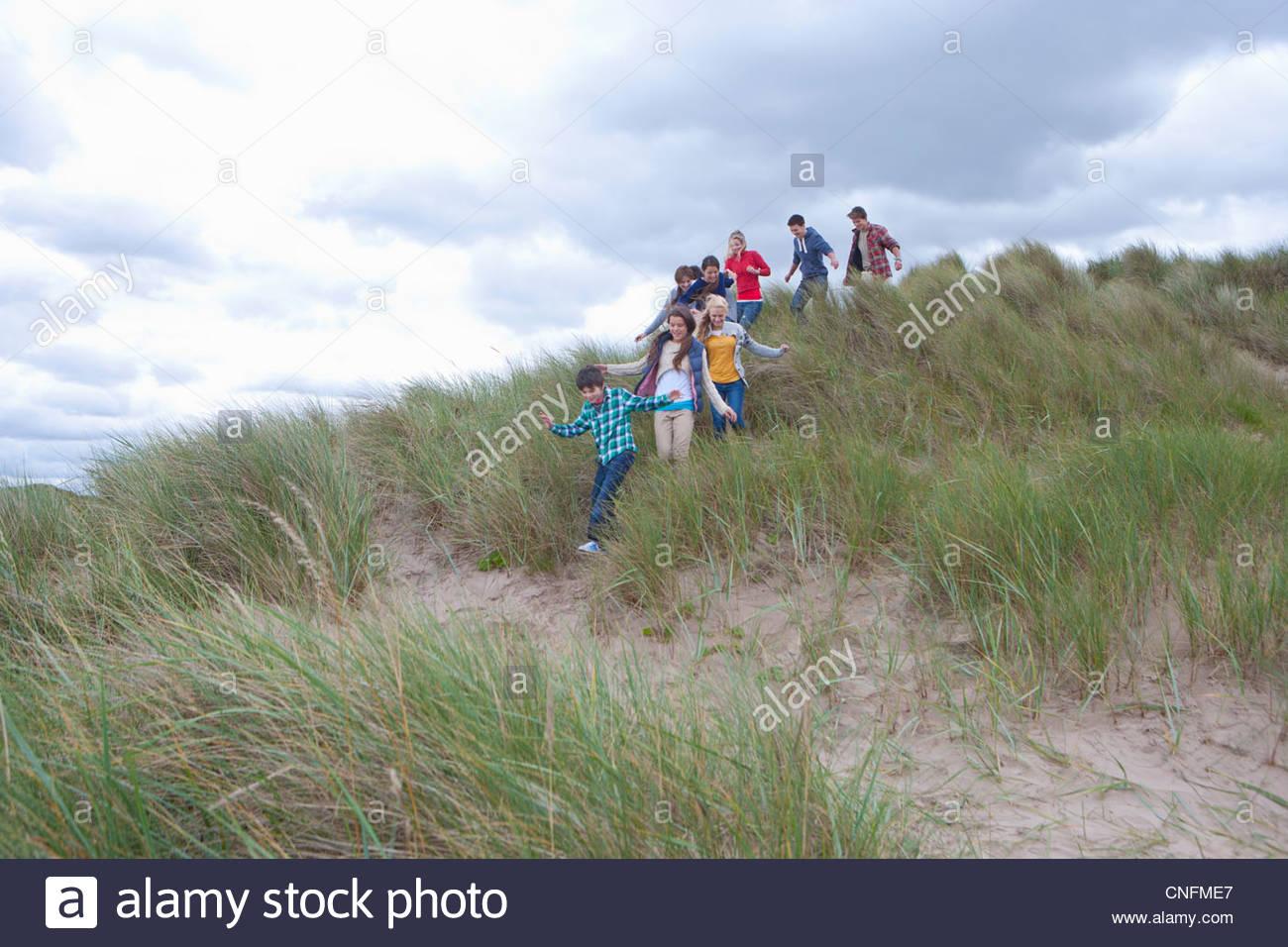 Teenage friends descending grass hill on beach - Stock Image