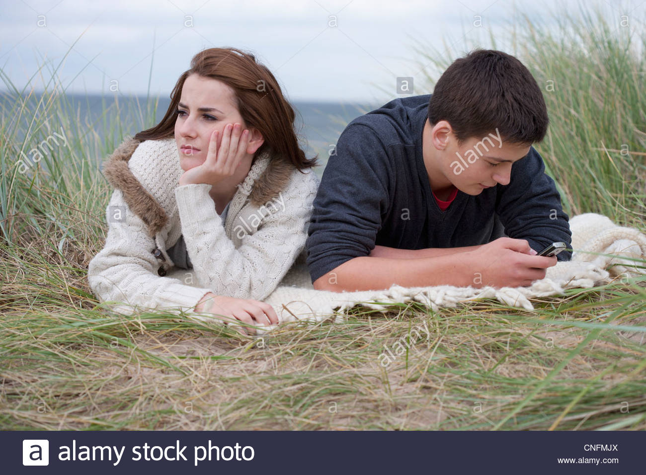 Teenage girl turning away from teenage boy text messaging on cell phone in grass on beach Stock Photo