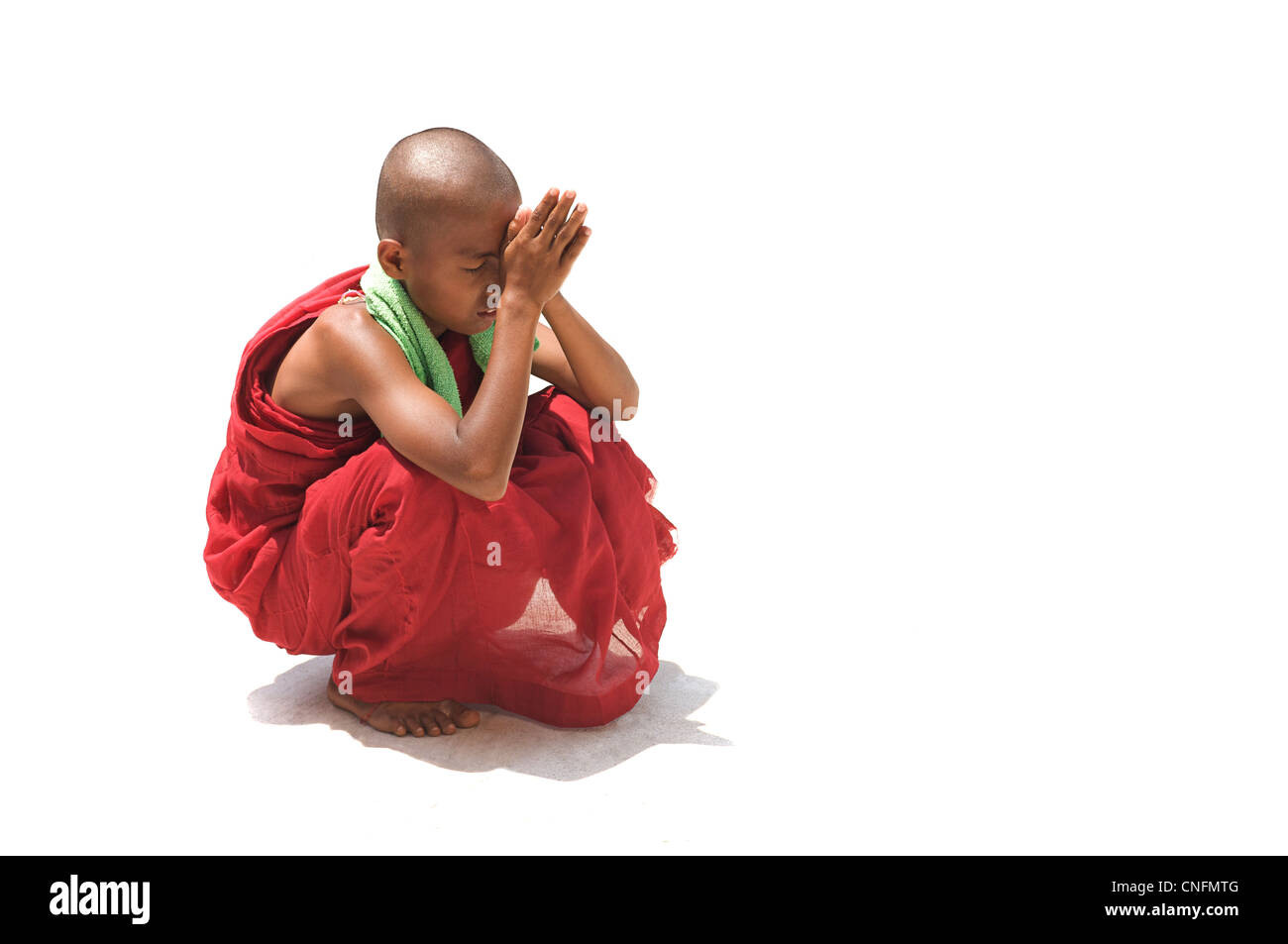 Young buddhist novice monk praying, Shwedagon Pagoda, Rangoon, Burma. Myanmar. White background - Stock Image