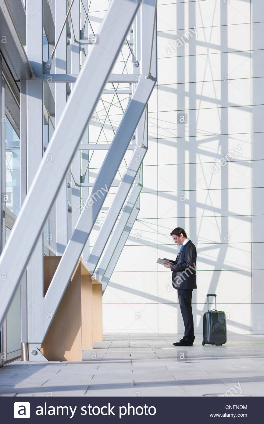 Businessman with suitcase using digital tablet in modern lobby - Stock Image