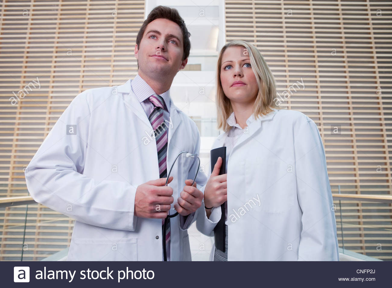 Portrait of serious doctors wearing lab coats in hospital corridor - Stock Image