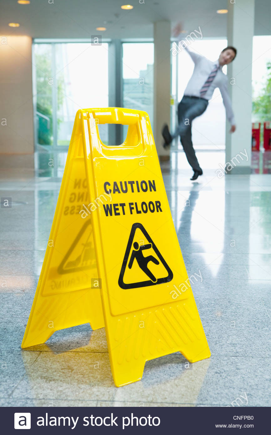 Businessman slipping behind wet floor sign in lobby - Stock Image