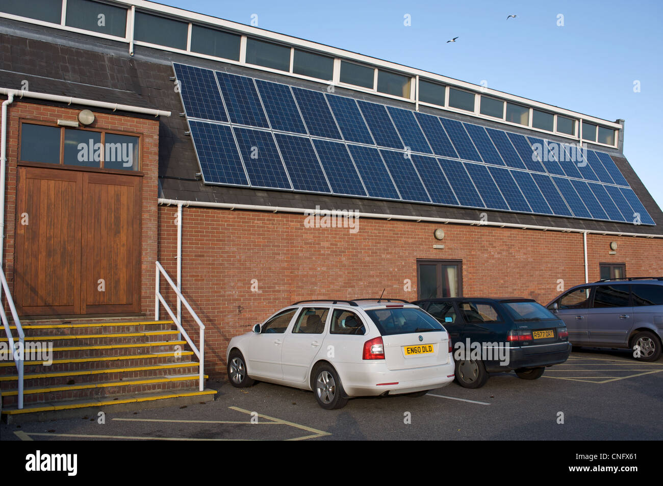 Solar panels fitted to the roof of a public building, UK. - Stock Image