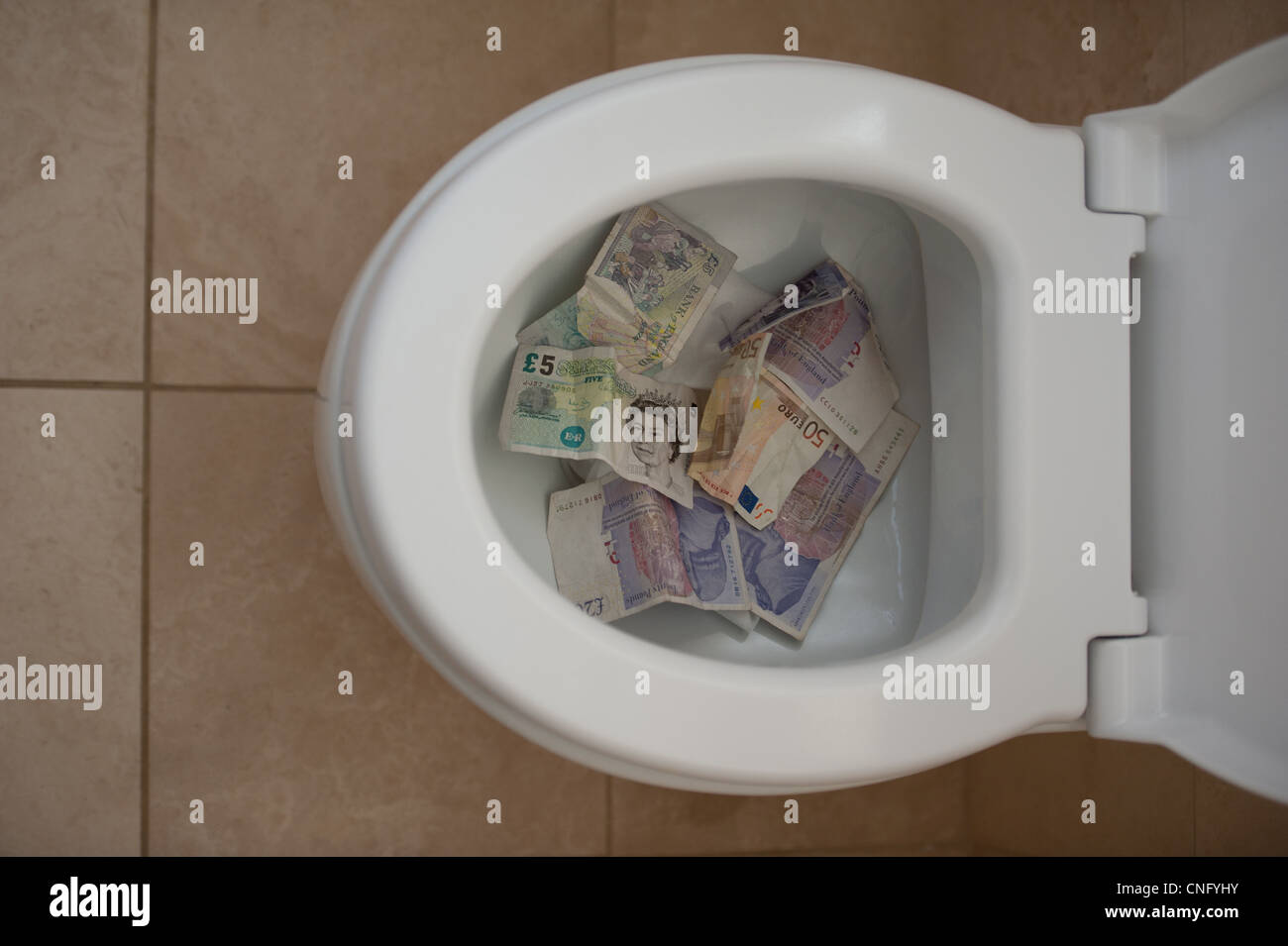 Financial crisis showing cash going down a toilet - Stock Image