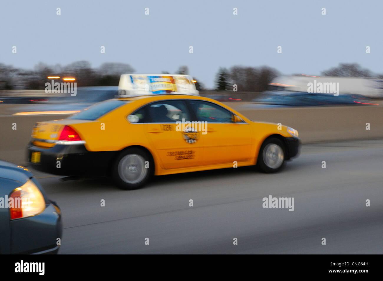 Orange taxicab speeding down expressway at dusk. - Stock Image
