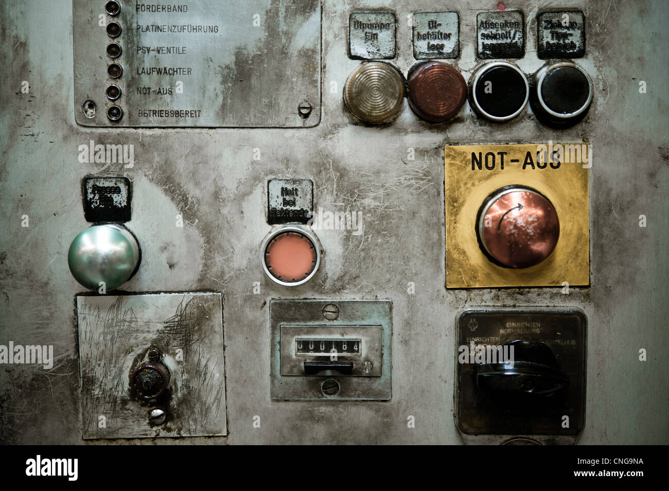 A dirty oily panel of an old machine in a factory with couple of buttons and knobs - Stock Image
