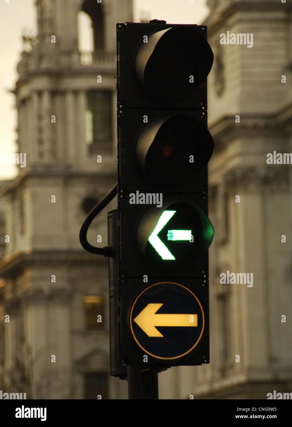 United Kingdom. England. London. Green light for vehicles that turn left. - Stock Image