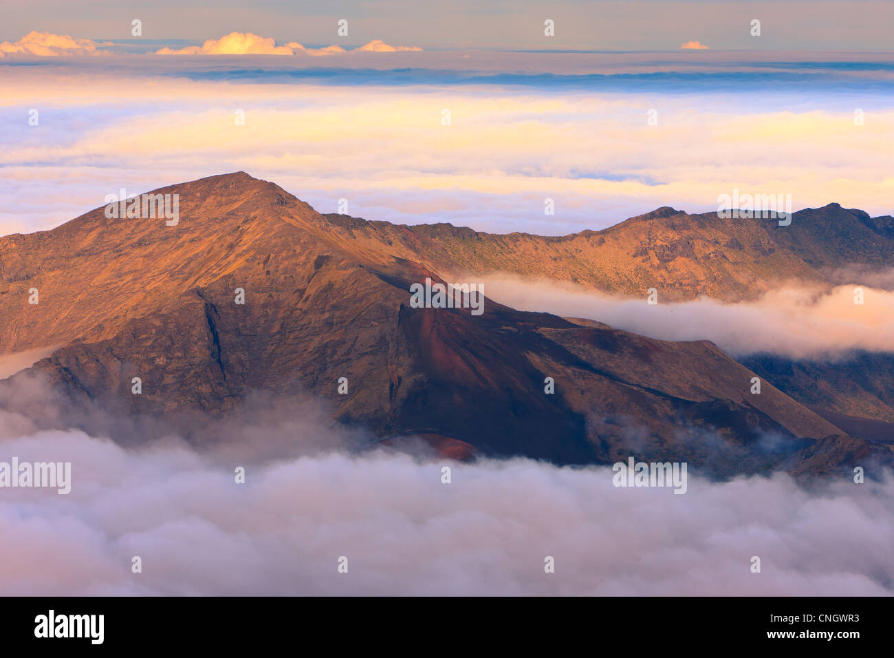 Sunset above the clouds over 3000 meters at the Haleakala Volcano, Maui, Hawaii - Stock Image