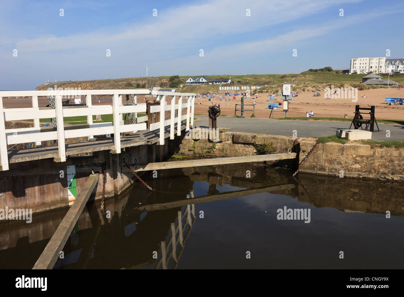 End of Bude canal by only hand operated sea lock gates in England with Summerleaze beach beyond in Bude, Cornwall, - Stock Image