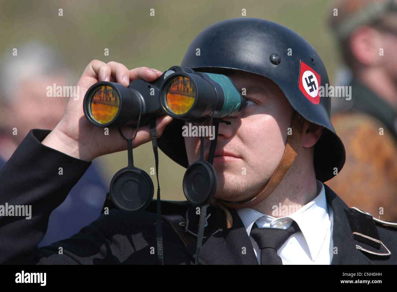 Nazi soldier looks through binocular produced in Russia. Re-enactment of the Battle for Orechov (1945) in Orechov - Stock Image