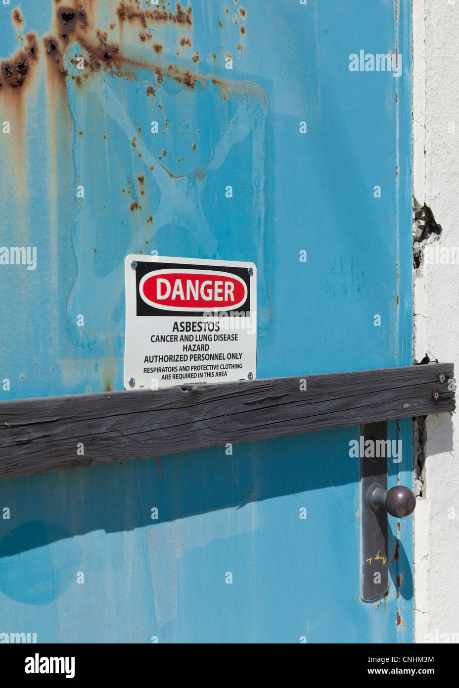 Asbestos warning sign posted on door - Stock Image