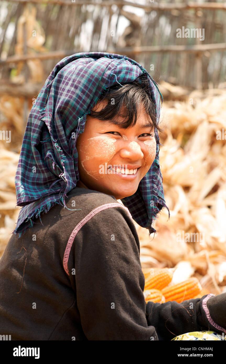 Burmese woman with distinctve Burmese make up called Thanaka on her face, near Pakokku, Burma - Stock Image