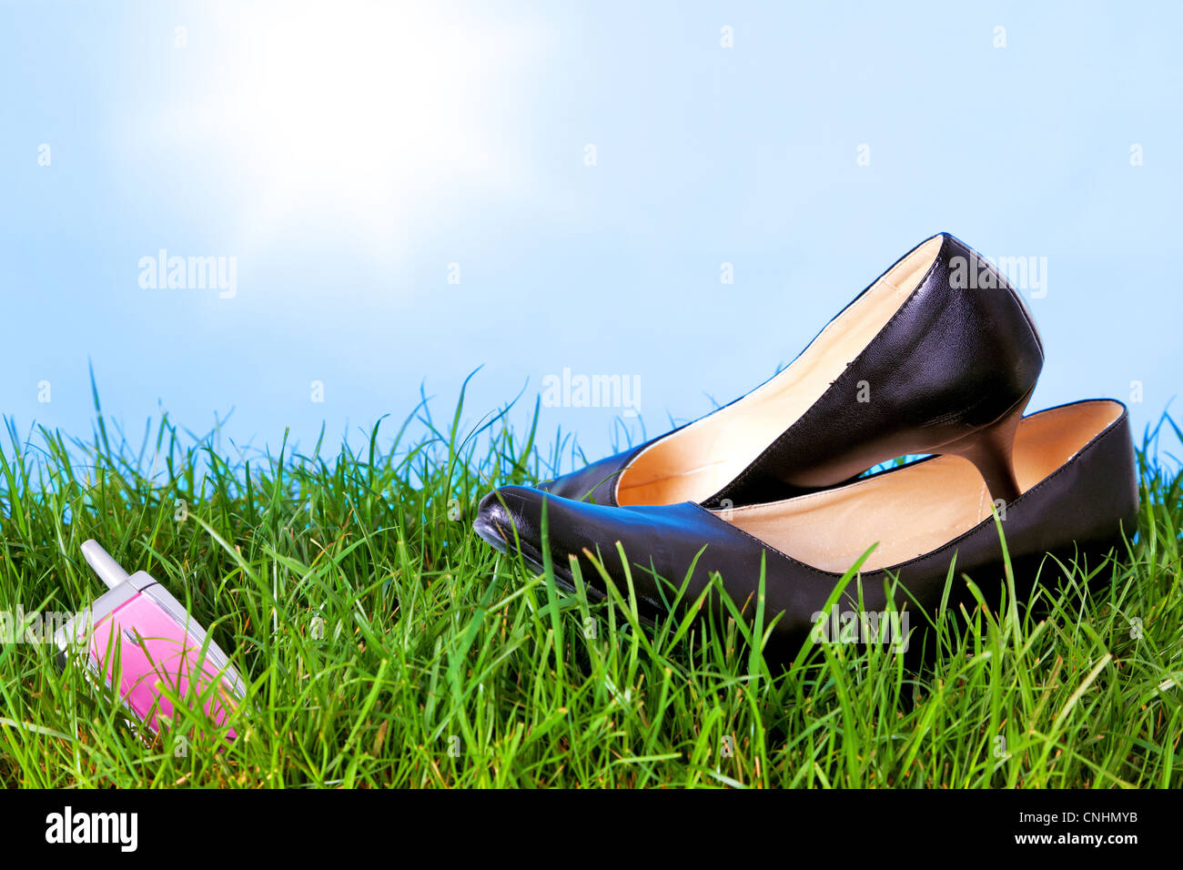 Photo of womens high heel shoes and a mobile phone on grass against a bright blue sky with sunshine. - Stock Image