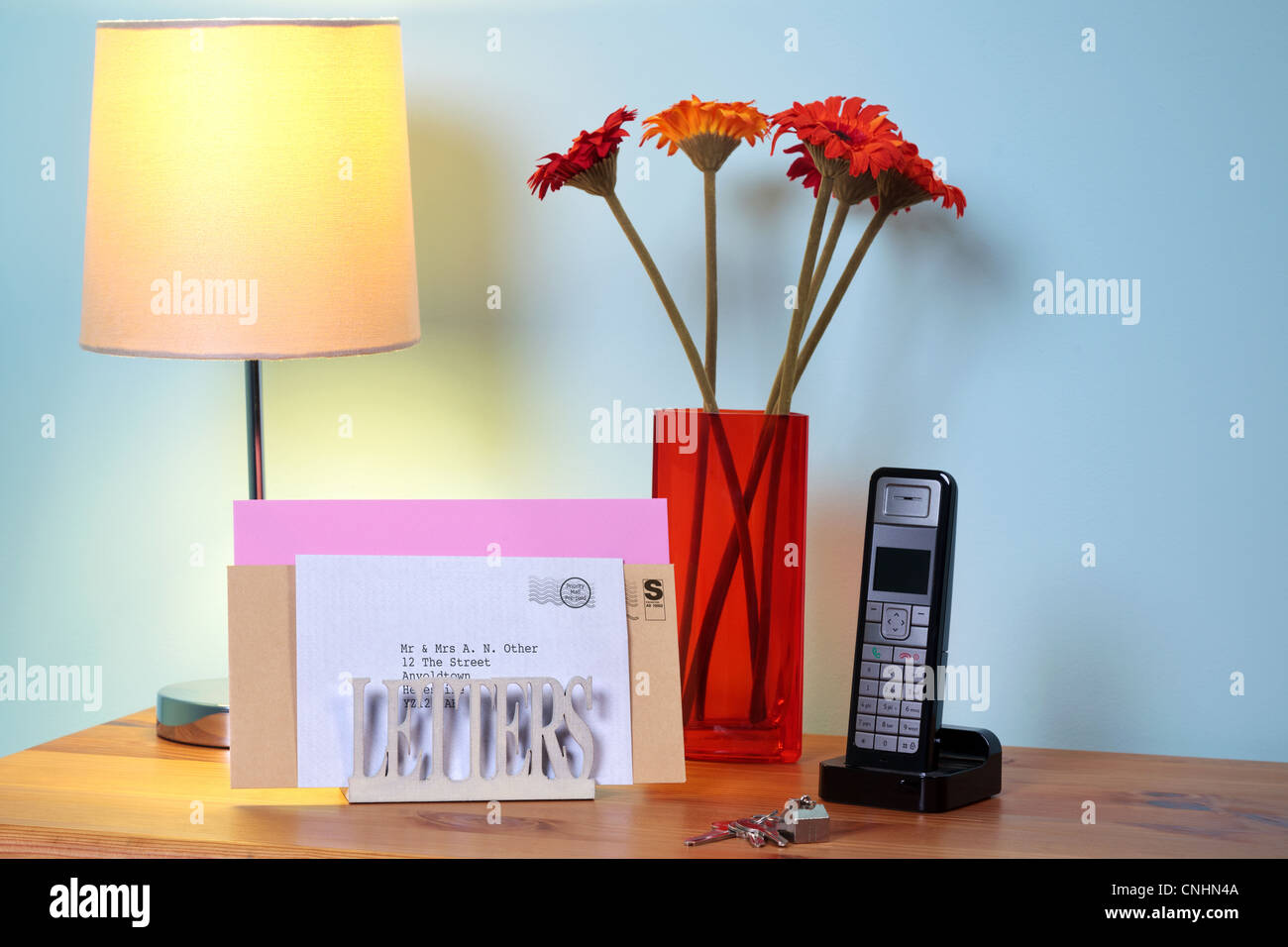 Photo of a letter rack with mail on a hall table. - Stock Image