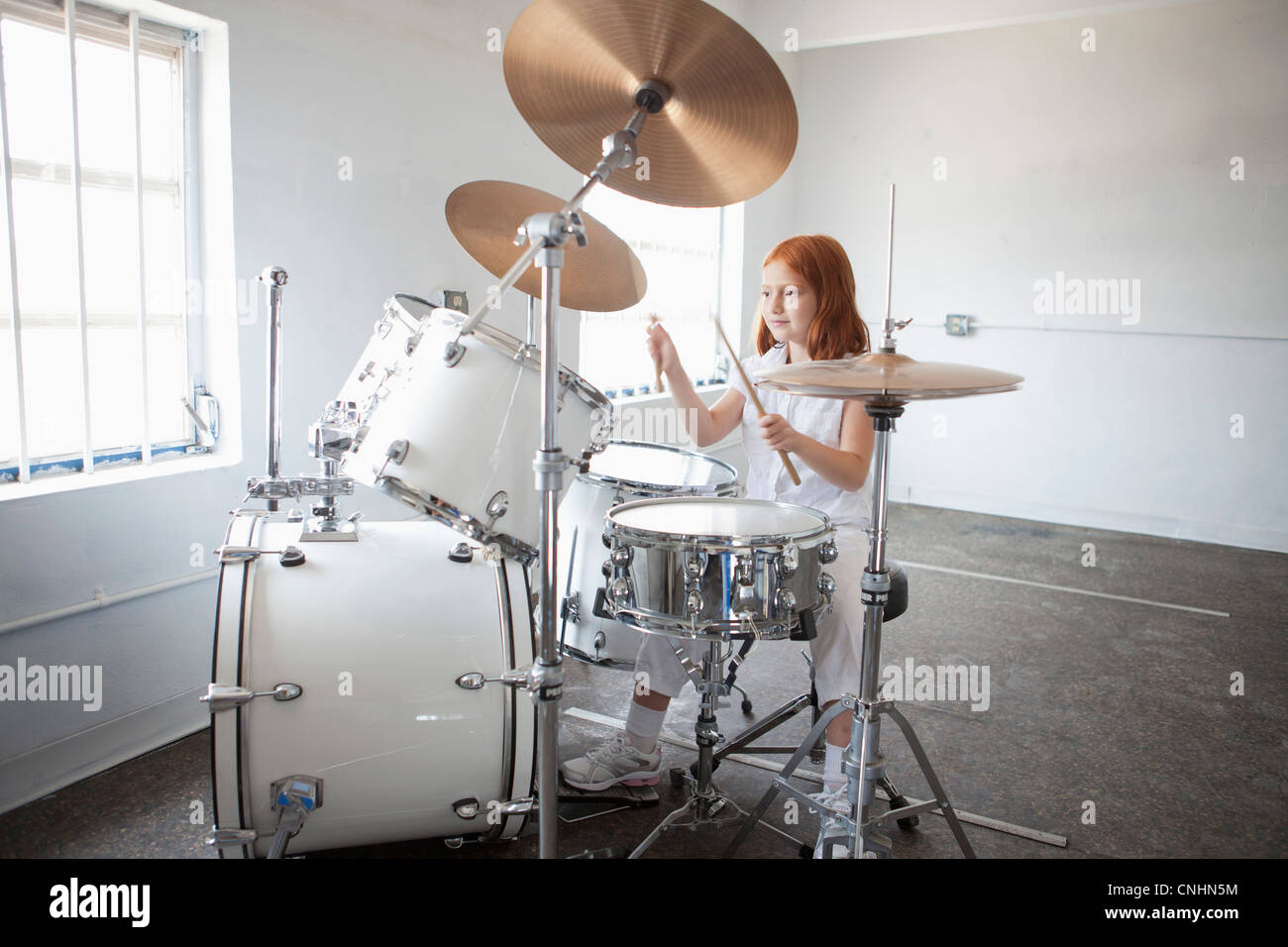 Girl plays drum kit - Stock Image