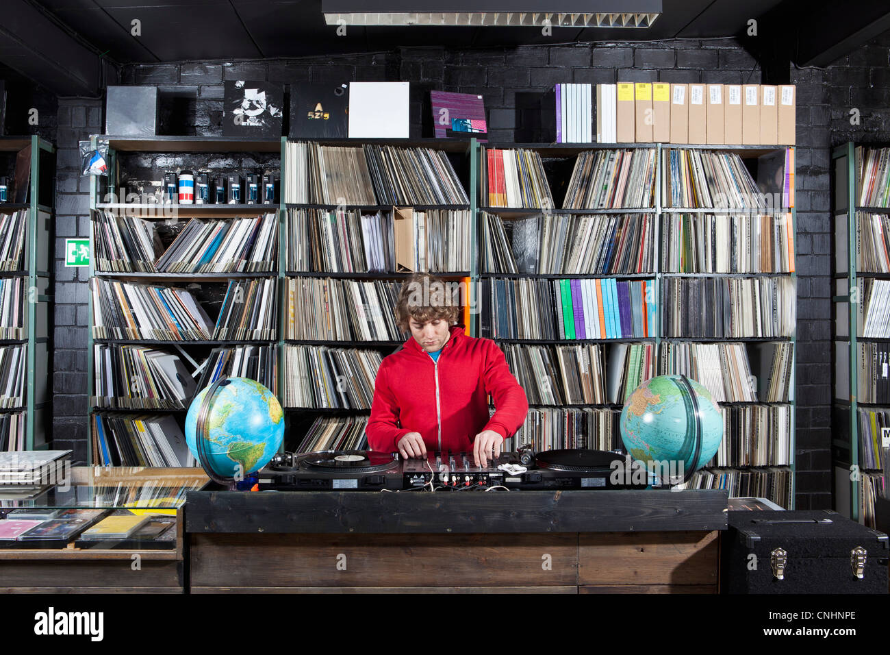 A young man using a sound mixer and DJ decks at a record store - Stock Image