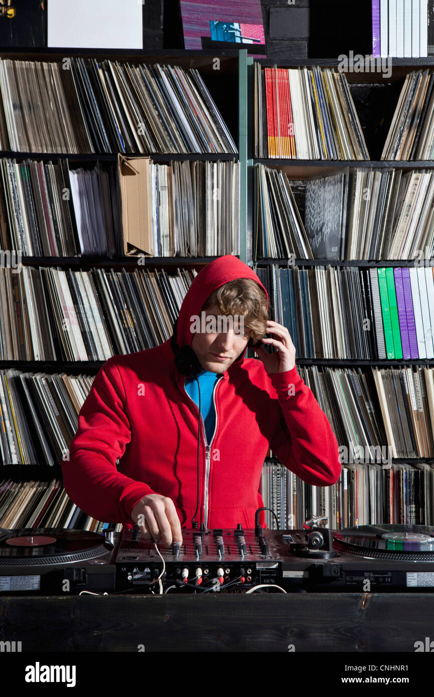 A young man using decks and a sound mixer at a record store - Stock Image