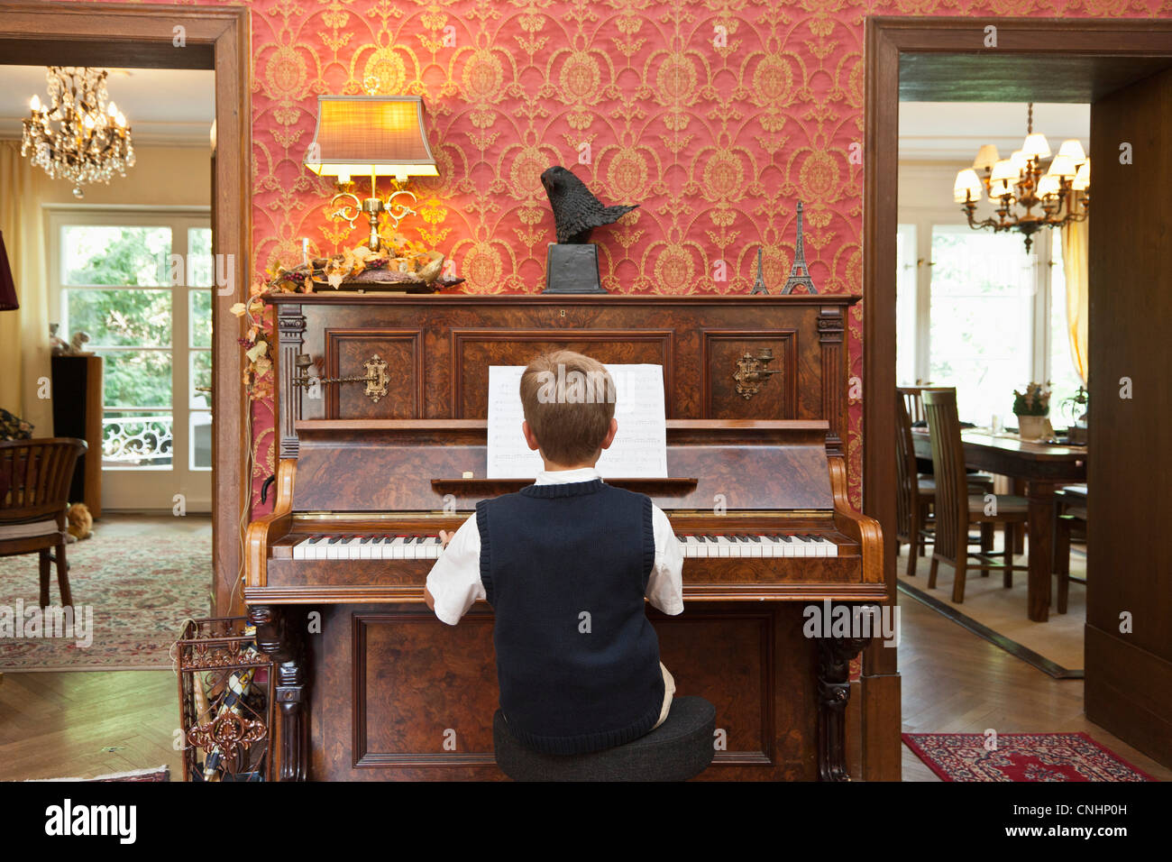 A boy practicing on an old-fashioned upright piano - Stock Image