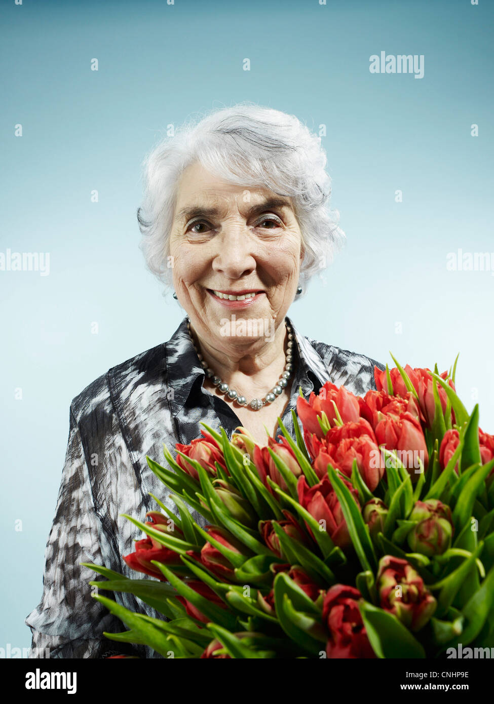 A senior woman receiving a bouquet of tulips Stock Photo