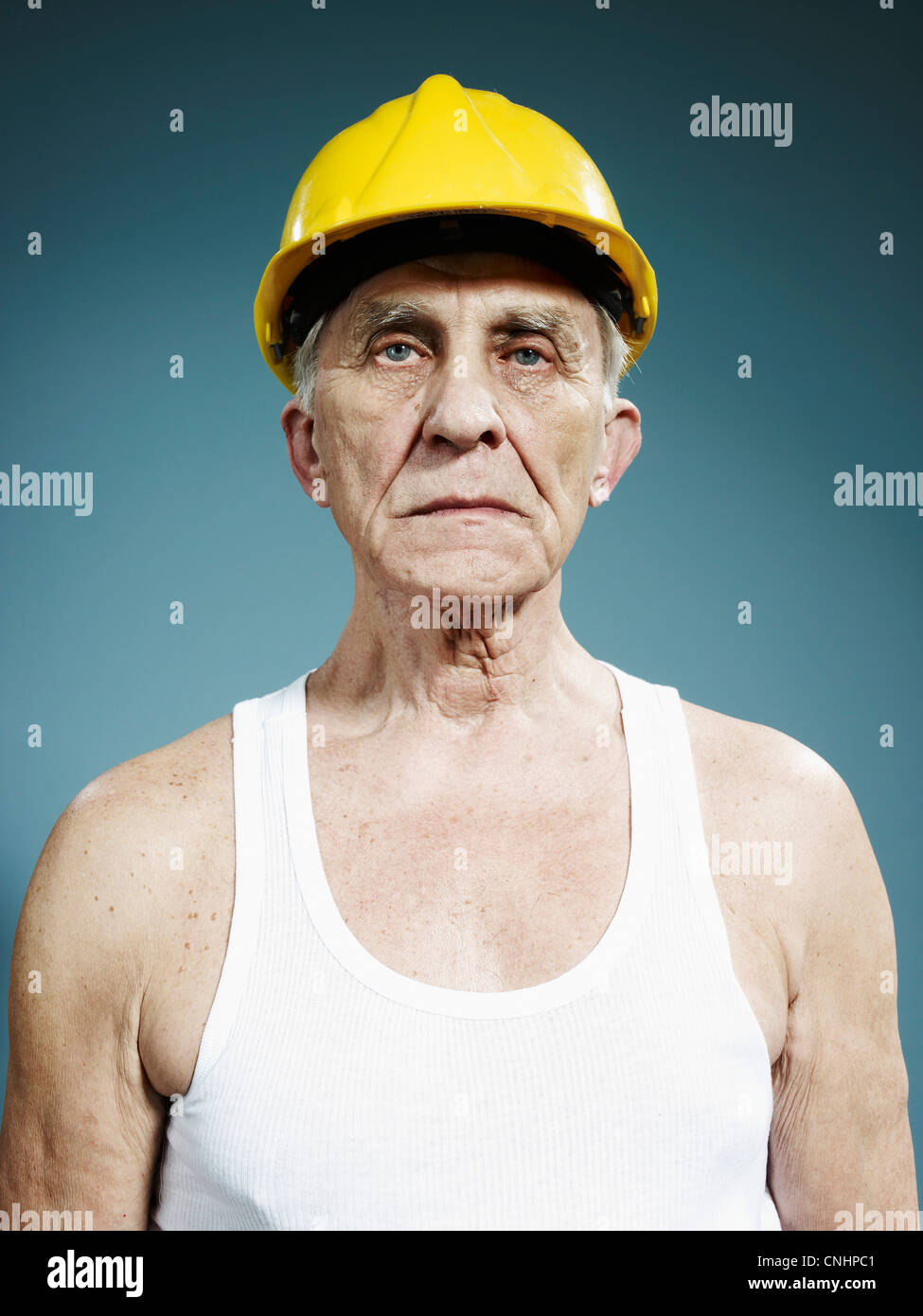 A serious senior man wearing a hardhat and tank top - Stock Image