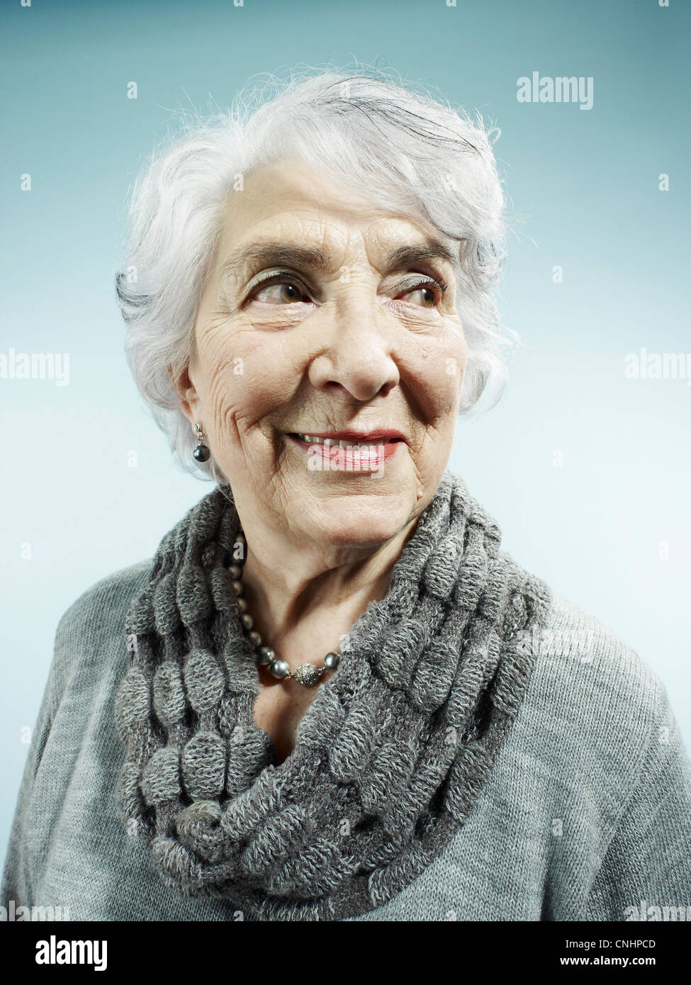 An elegant senior woman smiling and looking away - Stock Image